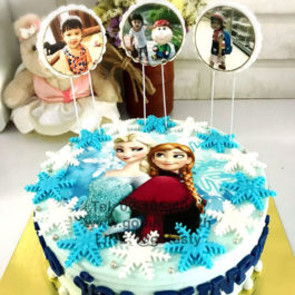 Blue and white photo cake of princess Elsa and Anna from Frozen with snow decoration