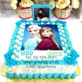 White and blue photo cake of princess Elsa and Anna from Frozen with bow and snow decorations