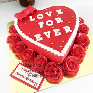 Red cream cake with rose and bow decorations